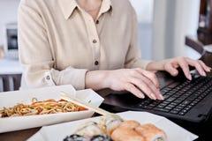 Vrouw die Aziatisch voedsel proeven op het werk stock foto