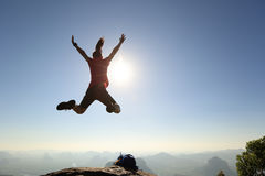 Vrouw die backpacker op de bovenkant van de zonsopgangberg springen Stock Foto