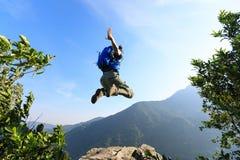 Vrouw die backpacker op klippenrand springen Royalty-vrije Stock Foto's