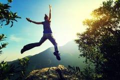 Vrouw die backpacker op klippenrand springen Stock Afbeelding