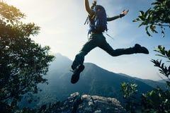 Vrouw die backpacker op klippenrand springen Royalty-vrije Stock Afbeelding