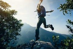 Vrouw die backpacker op klippenrand springen Stock Foto's