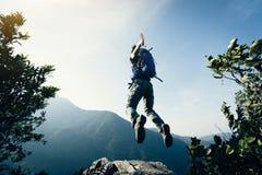Vrouw die backpacker op klippenrand springen Royalty-vrije Stock Foto