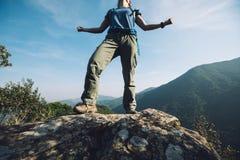 Vrouw die backpacker zich op klippenrand bevinden Royalty-vrije Stock Afbeeldingen