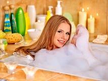 Vrouw die bad met heel wat schuim nemen stock foto