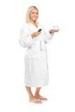 Vrouw die in badjas een een koffiekop en telefoon houdt stock afbeeldingen