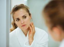 Vrouw die in badjas haar gezicht in spiegel controleert stock fotografie