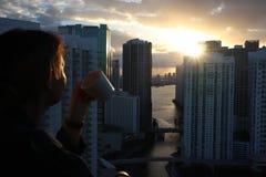 Vrouw die in badjas Haar ochtendkoffie of thee op een balkon drinken van de binnenstad Mooie zonsopgang in Miami van de binnensta stock afbeelding