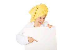 Vrouw die in badjas lege banner houden Stock Afbeeldingen
