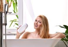 Vrouw die in badkuip liggen die bad dichtbij open badkamersvenster en washand met zachte de roomlotion van het douchegel nemen Royalty-vrije Stock Foto's