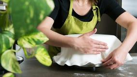 vrouw die in bakkerij cake met koninklijk suikerglazuur verfraaien royalty-vrije stock foto