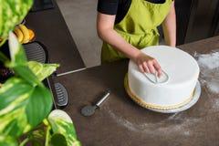 Vrouw die in bakkerij huwelijkscake met wit hierboven fondantje, mening verfraaien van stock afbeelding
