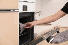 Vrouw die bakseldienblad zetten in elektrische oven in keuken stock foto's