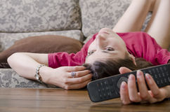 Vrouw die in bank op TV letten Stock Fotografie