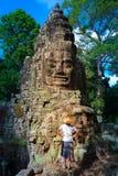 Vrouw die in Bayon-Tempel steengezichten bekijken, Angkor Thom, ochtend lichte duidelijke blauwe hemel Het wereldberoemde concept royalty-vrije stock fotografie