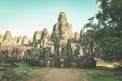 Vrouw die in Bayon-Tempel steengezichten bekijken, Angkor Thom, ochtend lichte duidelijke blauwe hemel Het wereldberoemde concept stock afbeelding