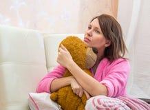 vrouw die in bed een teddybeer koesteren royalty-vrije stock fotografie