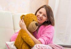 vrouw die in bed een teddybeer koesteren Royalty-vrije Stock Afbeelding
