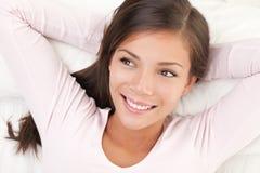 Vrouw die in bed glimlacht