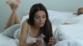 Vrouw die in bed liggen die condoom of mondelinge pillen kiezen, geboortenbeperkingsmethodes, veilig geslacht stock video