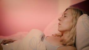 Vrouw die in bed liggen die verstoord smartphonegevoel bekijken en de telefoon zetten neer terwijl het zuchten stock videobeelden