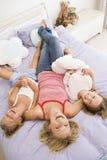 Vrouw die in bed met twee het jonge meisjes lachen ligt royalty-vrije stock foto's