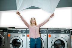 Vrouw die bedsheet in de wasserij maken stock fotografie