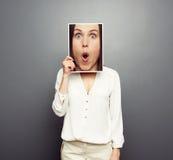 Vrouw die beeld behandelen met groot verbaasd gezicht Royalty-vrije Stock Afbeelding