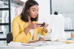 Vrouw die beeld van schets op smartphone nemen op het werk stock foto's