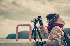 Vrouw die beelden op kustlijn nemen stock afbeeldingen