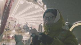 Vrouw die Beelden van Europese carrouselscène nemen op Smartphone 4K Meisje die van het seizoen van de de wintervakantie genieten stock videobeelden