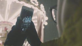 Vrouw die Beelden van Europese carrouselscène nemen op Smartphone 4K Meisje die van het seizoen van de de wintervakantie genieten stock video