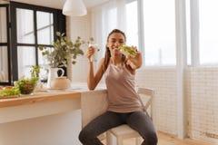 Vrouw die beenkappen en sportbovenkant dragen die van gezonde snack genieten royalty-vrije stock foto