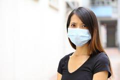 Vrouw die beschermend gezichtsmasker dragen Royalty-vrije Stock Foto