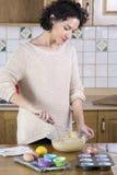 Vrouw die beslag in keuken zwaaien Stock Foto's