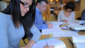 Vrouw die in bibliotheek met een groep bestuderen stock footage