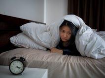 Vrouw die bij bed het awaking, slapeloosheidsconcept liggen stock foto