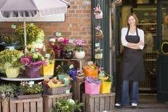Vrouw die bij bloemwinkel het glimlachen werkt Royalty-vrije Stock Afbeelding