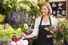 Vrouw die bij bloemwinkel het glimlachen werkt Royalty-vrije Stock Foto