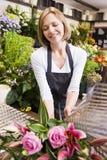 Vrouw die bij bloemwinkel het glimlachen werkt Stock Afbeelding