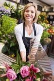 Vrouw die bij bloemwinkel het glimlachen werkt Stock Foto's