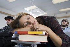 Vrouw die bij Bureaus in Klaslokaal rusten stock foto