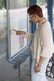 Vrouw die bij bushalte tijdschema bekijken royalty-vrije stock afbeelding