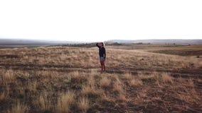 Vrouw die bij camera golft en in afstand bij de landweg kijkt stock footage