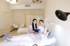 Vrouw die bij cosmetologistkabinet dichtbij arts en verpleegster liggen Royalty-vrije Stock Foto