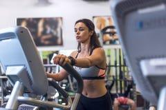 Vrouw die bij de gymnastiek in een elliptische opleiding van trainerCardio uitoefenen Stock Fotografie