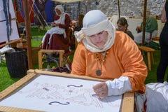 Vrouw die bij de middeleeuwse markt borduurt royalty-vrije stock foto
