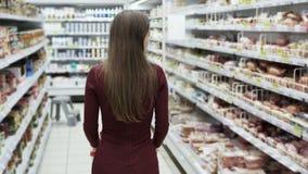 Vrouw die bij de supermarkt, achtereindmening winkelen, steadicam schot stock video