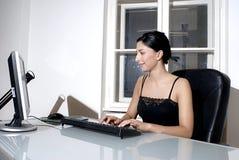 Vrouw die bij een bureau werkt Stock Afbeelding