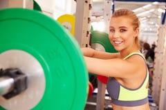 Vrouw die bij een hurkend rek in een gymnastiek, die aan camera leunen glimlachen stock fotografie